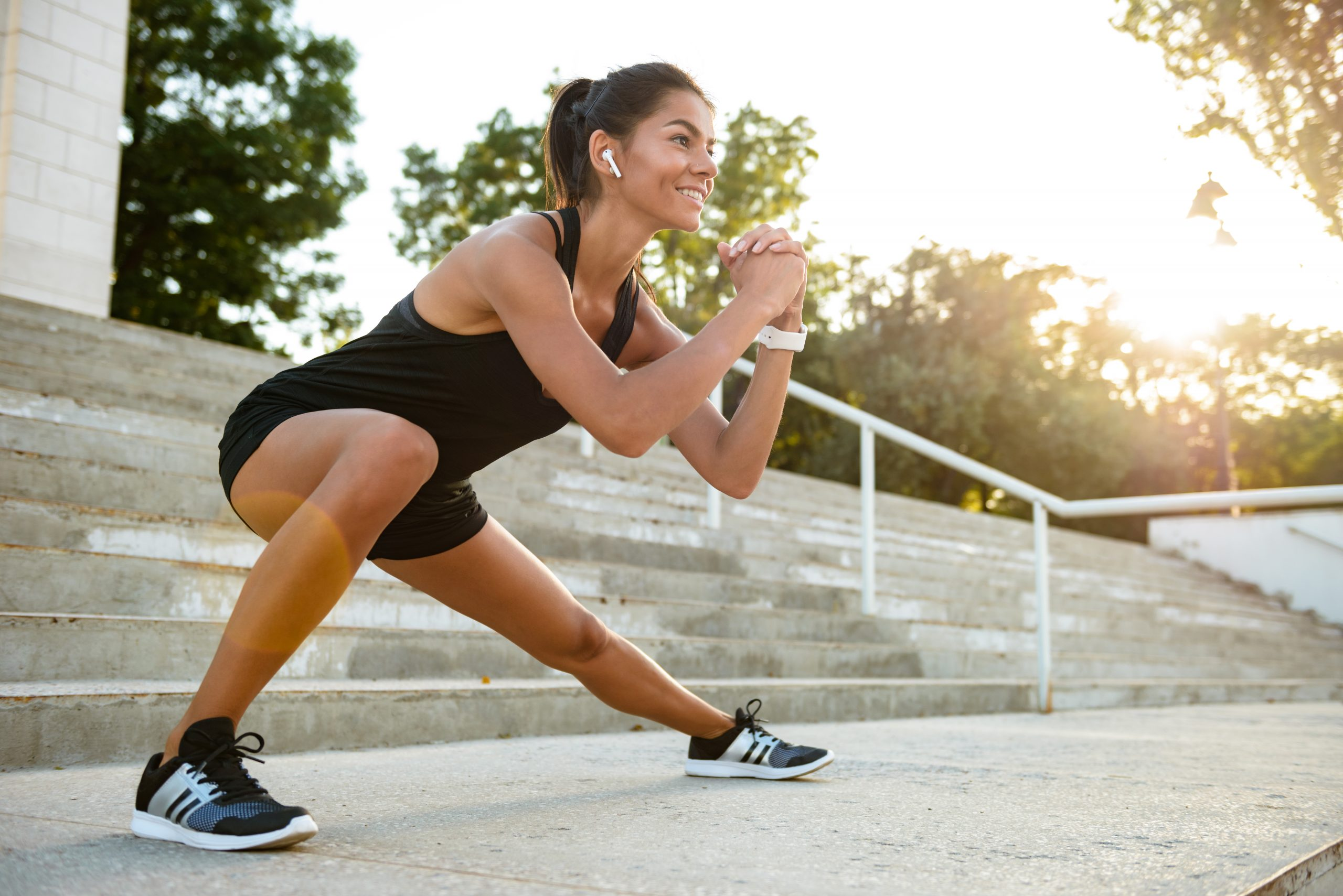 Portrait of a smiling fitness woman in earphones doing stretching exercises on stairs outdoors